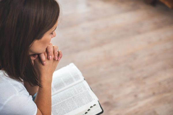 young woman pray with bible relationship with God at home